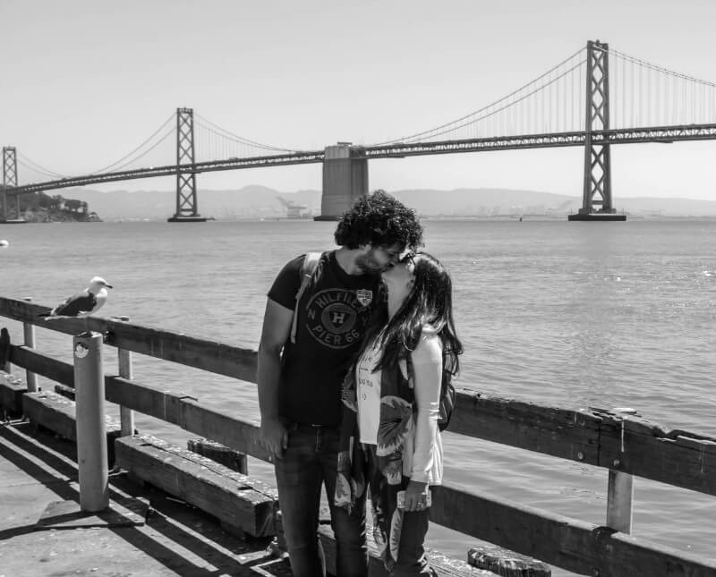 a couple kiss in front of the bay bridge